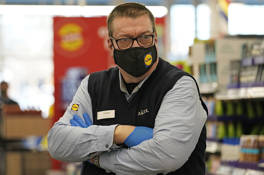 In this Thursday, Feb. 4, 2021 photo, Lidl grocery market supervisor Joseph Lupo pauses in an aisle at the store where he works in Lake Grove, N.Y., after getting the first dose of the coronavirus vaccine earlier in the day. Nearly two months after the U.S. began its COVID-19 vaccination drive, many grocery workers are still waiting their turn. At least 11 states are not prioritizing grocery workers at all, while many others have bumped them down in favor of people 65 and older, an effort to speed up the vaccination drive. (AP Photo/Kathy Willens)