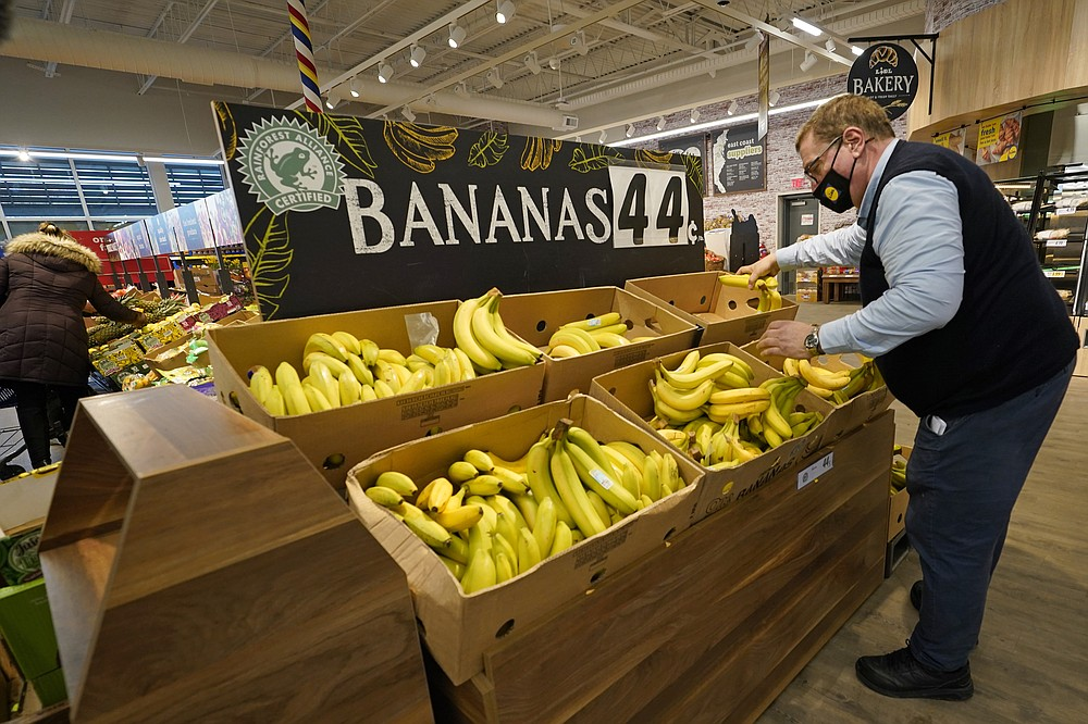 """Lidl employee Joseph Lupo, arranges bananas in the produce aisle of the market where he works, Thursday, Feb. 4, 2021, in Lake Grove, N.Y. Earlier in the day, Lupo received the first dose of the coronavirus vaccine. The German grocery chain is offering $200 to any employee who gets vaccinated as an incentive. Lupo, who fell ill with the virus in March, was elated to get his first vaccine dose. """"I never ever want to get COVID again, or see anybody else get it,"""" said Lupo, 59. (AP Photo/Kathy Willens)"""