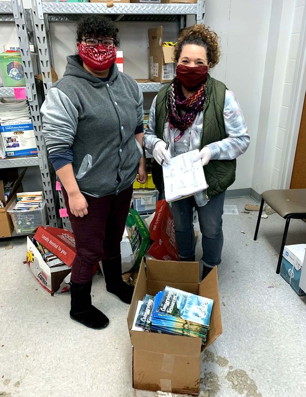 Photo submitted Volunteers Jazmin Rubio (left) and Michele Markovich help sort through damaged school supplies on Wednesday after Bright Futures donation room flooded.