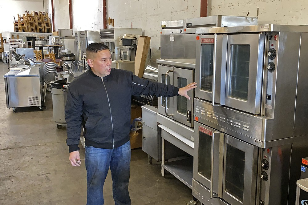 Jose Bonilla Jr. shows a used industrial oven for sale in the warehouse of his family's business, American Restaurant Supply in San Leandro, Calif., on Jan. 14, 2021. The pandemic has forced thousands of restaurants to permanently shut their doors as dining restrictions keep customers away. But the unprecedented closures have created a business boom for commercial auctioneers that buy and sell used restaurant equipment. (AP Photo/Terry Chea)