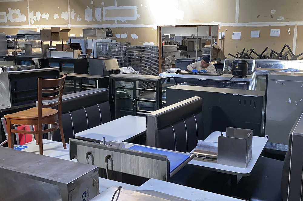 An employee cleans used equipment for sale inside the warehouse of American Restaurant Supply, which is packed with appliances and furniture from restaurants that have shut down during the pandemic, in San Leandro, Calif., on Jan. 14, 2021. The pandemic has forced thousands of restaurants to permanently shut their doors as dining restrictions keep customers away. But the unprecedented closures have created a business boom for commercial auctioneers that buy and sell used restaurant equipment. (AP Photo/Terry Chea)