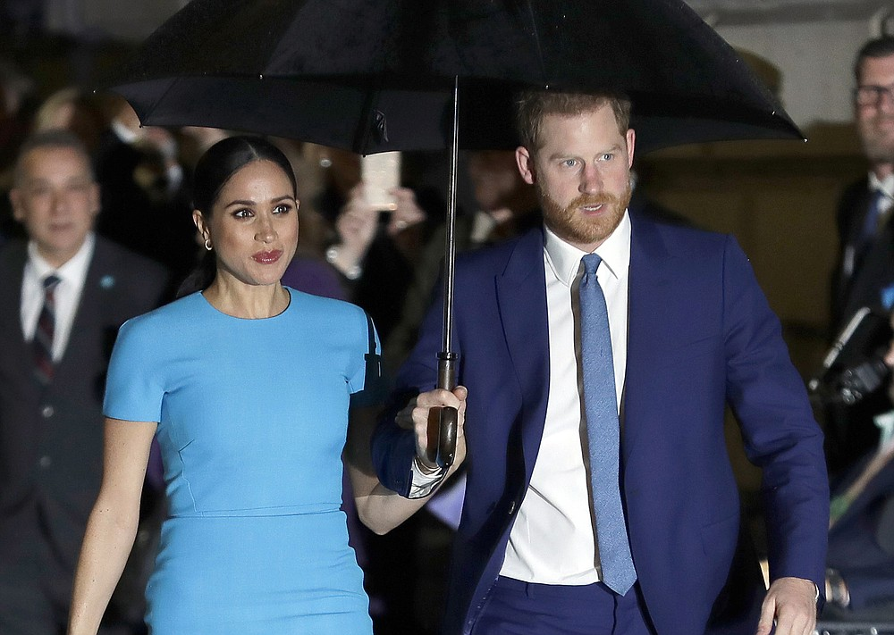FILE - In this March 5, 2020 file photo, Britain's Prince Harry and Meghan, Duchess of Sussex arrive at the annual Endeavour Fund Awards in London.  Harry and Meghan stepped away from full-time royal life in early 2020, and Buckingham Palace on Friday Feb. 19, 2021, confirmed the couple will not be returning to royal duties, and Harry will give up his honorary military titles. (AP Photo/Kirsty Wigglesworth, File)