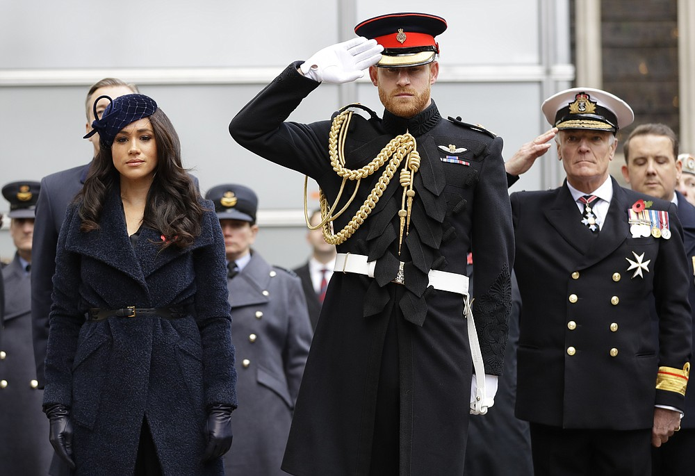 FILE - In this Nov. 7, 2019 file photo Britain's Prince Harry and Meghan, the Duchess of Sussex attend the 91st Field of Remembrance at Westminster Abbey in London. Harry and Meghan stepped away from full-time royal life in early 2020, and Buckingham Palace on Friday Feb. 19, 2021, confirmed the couple will not be returning to royal duties, and Harry will give up his honorary military titles. (AP Photo/Kirsty Wigglesworth, pool)