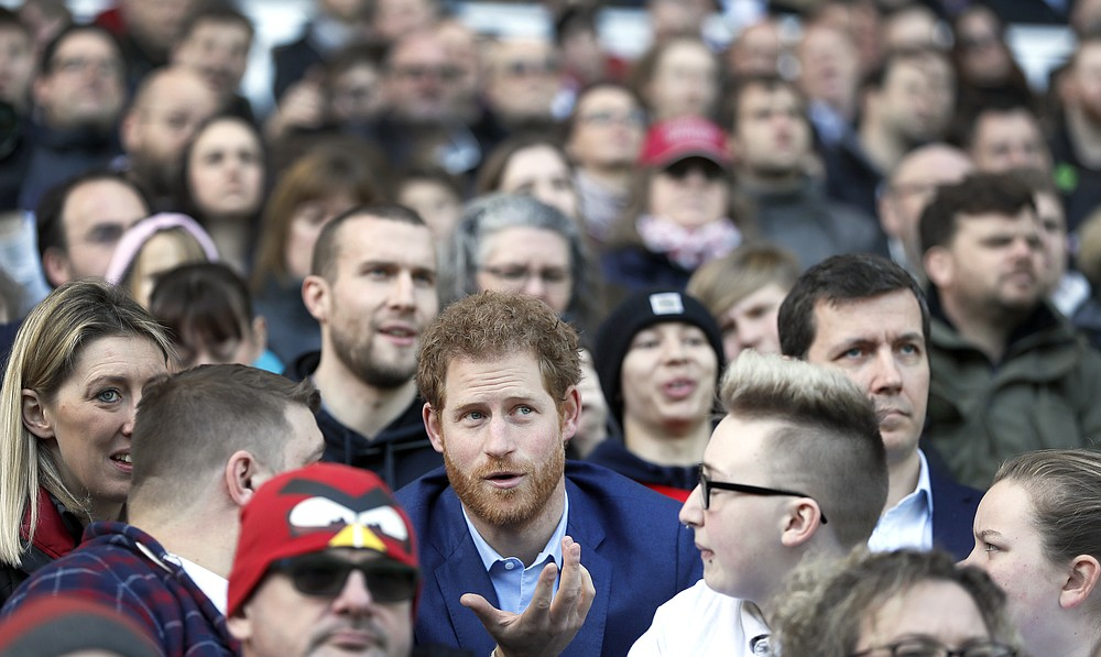 FILE - In this Feb. 17, 2017 file photo Britain's Prince Harry speaks with people from the RFU Try for Change programme during a visit to an England Rugby Squad training session at Twickenham Stadium in London. Harry and Meghan stepped away from full-time royal life in early 2020, and Buckingham Palace on Friday Feb. 19, 2021, confirmed the couple will not be returning to royal duties, and Harry will give up his honorary military titles. (AP Photo/Kirsty Wigglesworth, pool, File)
