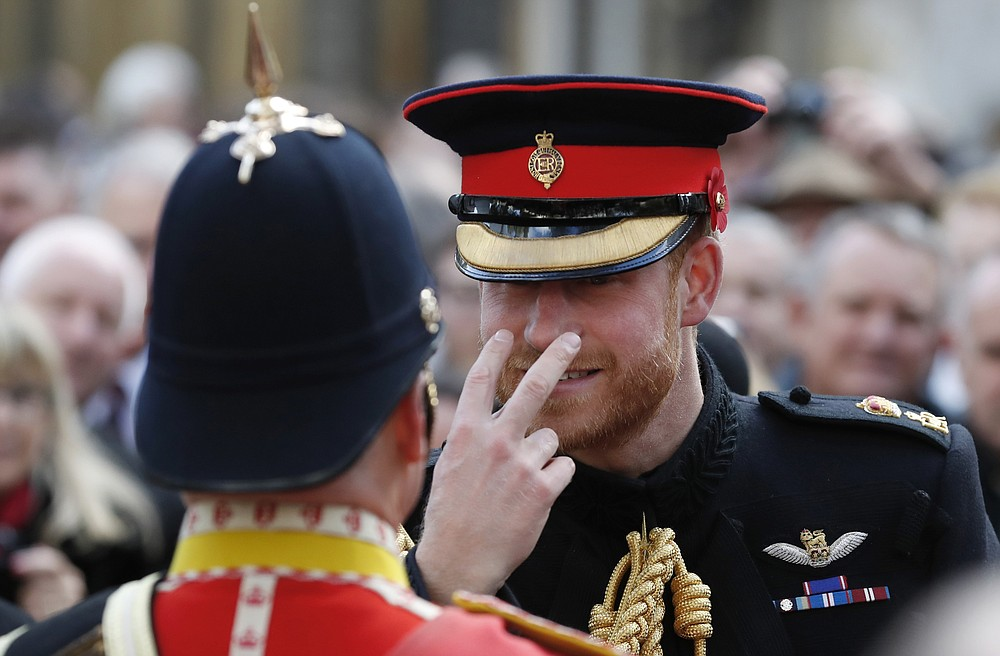FILE - In this Nov. 8, 2018 file photo Britain's Prince Harry gestures to a serviceman as he attends the annual Field of Remembrance service at Westminster Abbey in London. Harry and Meghan stepped away from full-time royal life in early 2020, and Buckingham Palace on Friday Feb. 19, 2021, confirmed the couple will not be returning to royal duties, and Harry will give up his honorary military titles. (AP Photo/Alastair Grant, File)