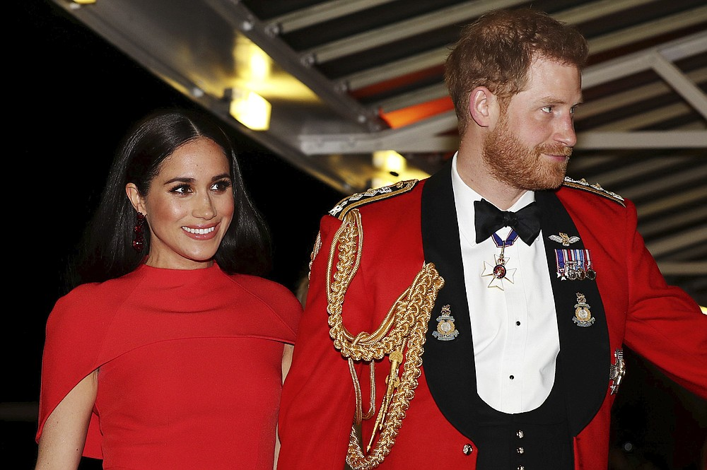 FILE - In this Saturday March 7, 2020 file photo, Britain's Prince Harry and Meghan, Duchess of Sussex arrive at the Royal Albert Hall in London, to attend the Mountbatten Festival of Music. Harry and Meghan stepped away from full-time royal life in early 2020, and Buckingham Palace on Friday Feb. 19, 2021, confirmed the couple will not be returning to royal duties, and Harry will give up his honorary military titles. (Simon Dawson/Pool via AP, file)