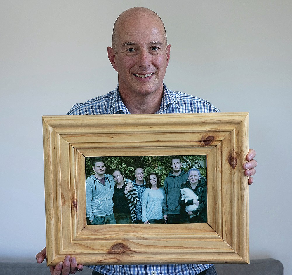 Jonathan Manning holds a photo of his children and their partners at his home in Christchurch, New Zealand, Wednesday, Feb. 10, 2021. Manning helped guide his teenage children through their grief after their mother Donna Manning was killed. One woman has used her anger to ensure buildings are safer. Others have found peace after heartbreaking losses. Ten years after an earthquake in Christchurch killed 185 people and devastated the city, some of those profoundly affected are sharing their journeys. (AP Photo/Peter Meecham)