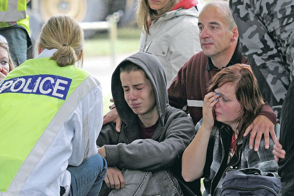 FILE - In this Feb 23, 2011, file photo, police inform Kent Manning, 15, second from left, Lizzy Manning, 18, right, and their father Jonathan Manning, there is no chance of survivors in the CTV building in Christchurch, New Zealand, after the city was hit by a 6.3 earthquake on Feb 22, 2011. One woman has used her anger to ensure buildings are safer. Others have found peace after heartbreaking losses. Ten years after an earthquake in Christchurch killed 185 people and devastated the city, some of those profoundly affected are sharing their journeys. (AP Photo/Rob Griffith, File)