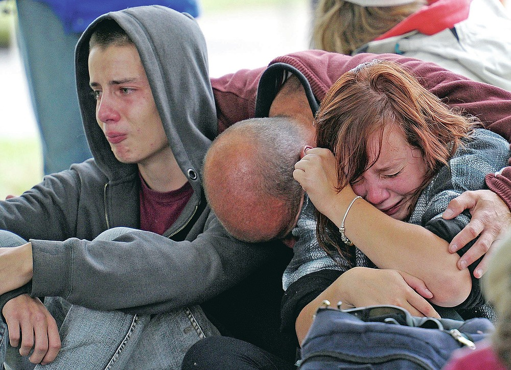 FILE - In this Feb 23, 2011, file photo, police inform Kent Manning, 15, left, Lizzy Manning, 18, right, and their father Jonathan, center, there is no chance of survivors in the CTV building in Christchurch, New Zealand, after the city was hit by a 6.3 earthquake on Feb 22, 2011. One woman has used her anger to ensure buildings are safer. Others have found peace after heartbreaking losses. Ten years after the earthquake in Christchurch killed 185 people and devastated the city, some of those profoundly affected are sharing their journeys. (AP Photo/Rob Griffith, File)