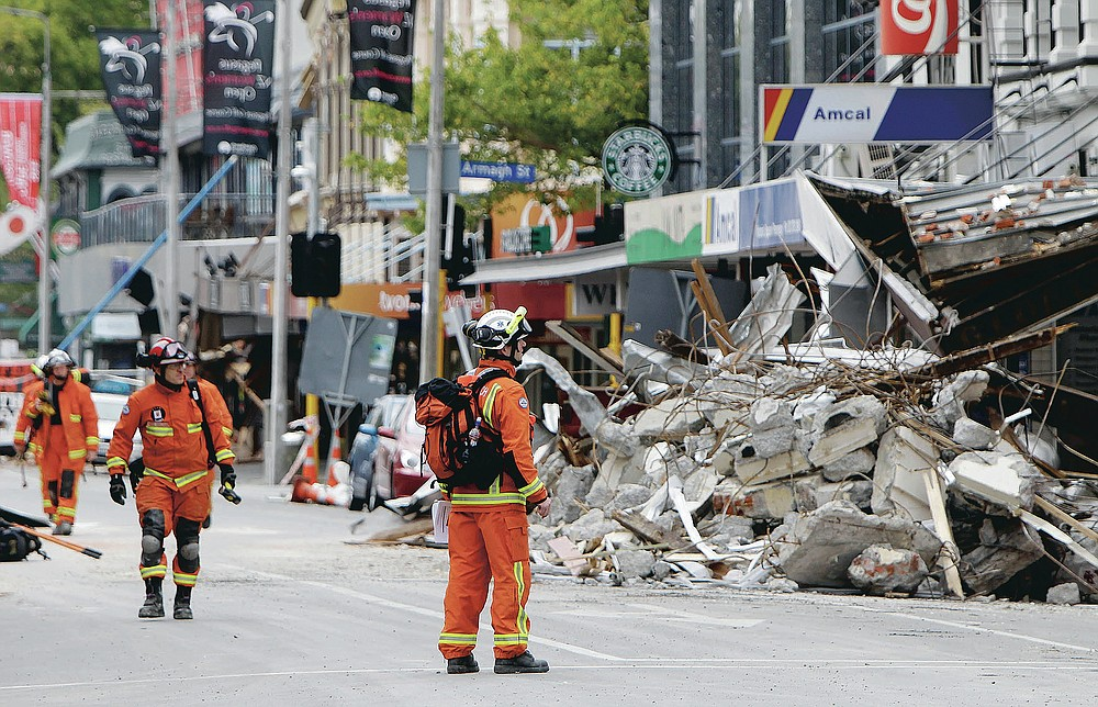 FILE - In this Feb. 26, 2011, file photo, representatives from the United Kingdom Fire and Rescue Service inspect the earthquake-damaged buildings in Colombo Street, Christchurch, New Zealand. One woman has used her anger to ensure buildings are safer. Others have found peace after heartbreaking losses. Ten years after the earthquake in Christchurch killed 185 people and devastated the city, some of those profoundly affected are sharing their journeys. (AP Photo/Mark Baker, File)