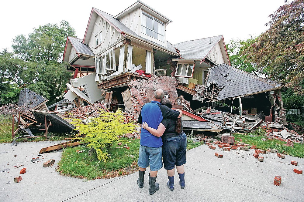 FILE - In this Feb. 23, 2011, file photo, Murray James, left, and Kelly James look at their destroyed house in central Christchurch, New Zealand, a day after a deadly earthquake. One woman has used her anger to ensure buildings are safer. Others have found peace after heartbreaking losses. Ten years after the earthquake in Christchurch killed 185 people and devastated the city, some of those profoundly affected are sharing their journeys. (AP Photo/Mark Baker, File)