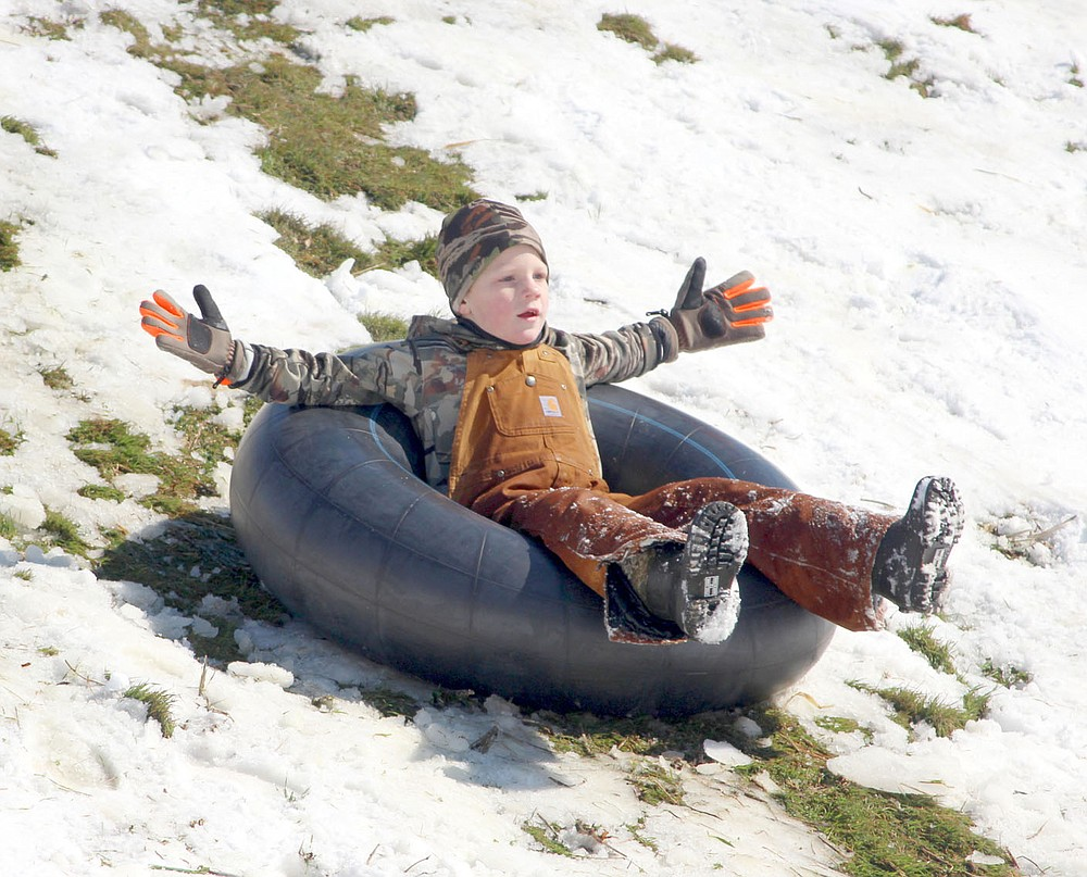 Keith Bryant/The Weekly Vista Bentley Daylong, 6, splays out as he rides a tube down the snow-slicked Lake Ann dam after last week's snowstorm.