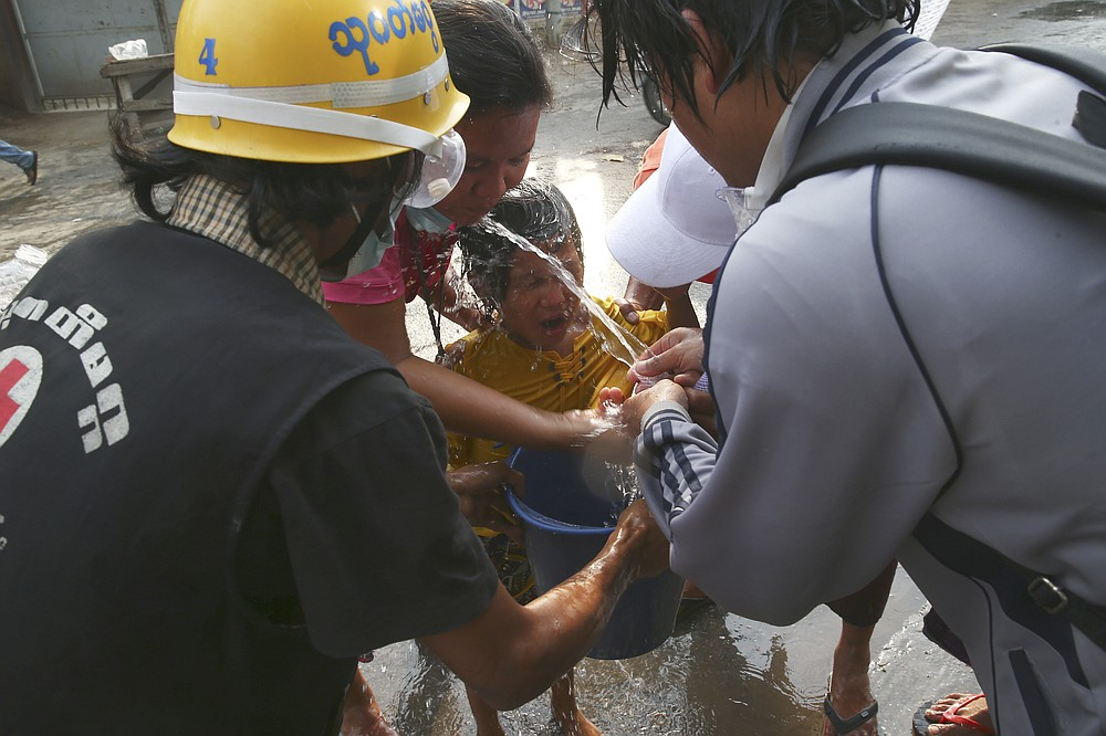 People hose their faces with water after tear gas was used in dispersing a protest in Mandalay, Myanmar on Saturday, Feb. 20, 2021. Security forces in Myanmar ratcheted up their pressure against anti-coup protesters Saturday, using water cannons, tear gas, slingshots and rubber bullets against demonstrators and striking dock workers in Mandalay, the nation's second-largest city. (AP Photos)