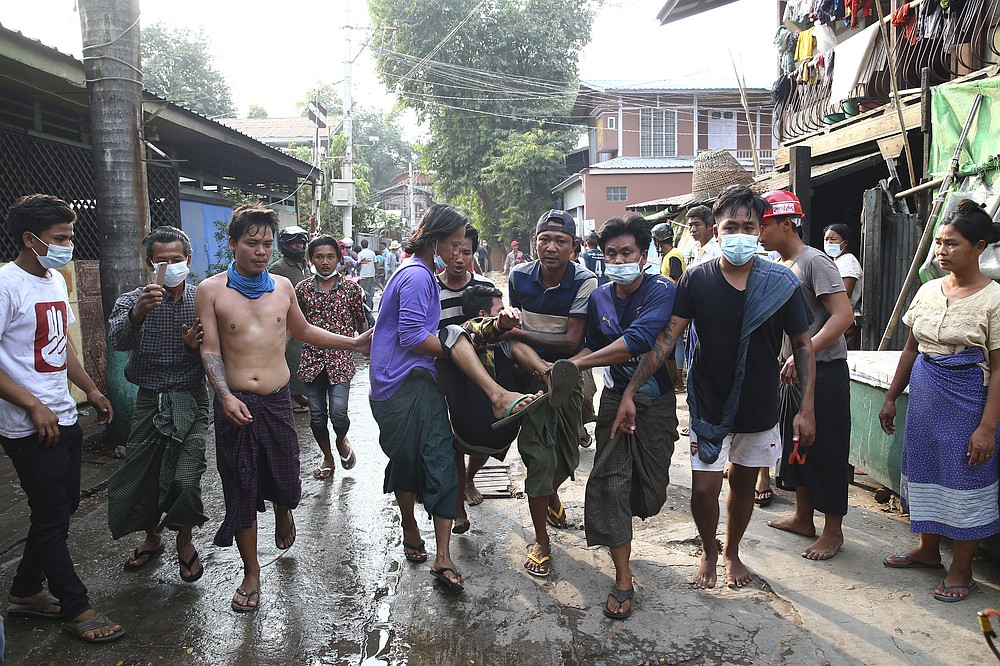 A man is carried after police dispersed protesters in Mandalay, Myanmar on Saturday, Feb. 20, 2021. Security forces in Myanmar ratcheted up their pressure against anti-coup protesters Saturday, using water cannons, tear gas, slingshots and rubber bullets against demonstrators and striking dock workers in Mandalay, the nation's second-largest city. (AP Photos)