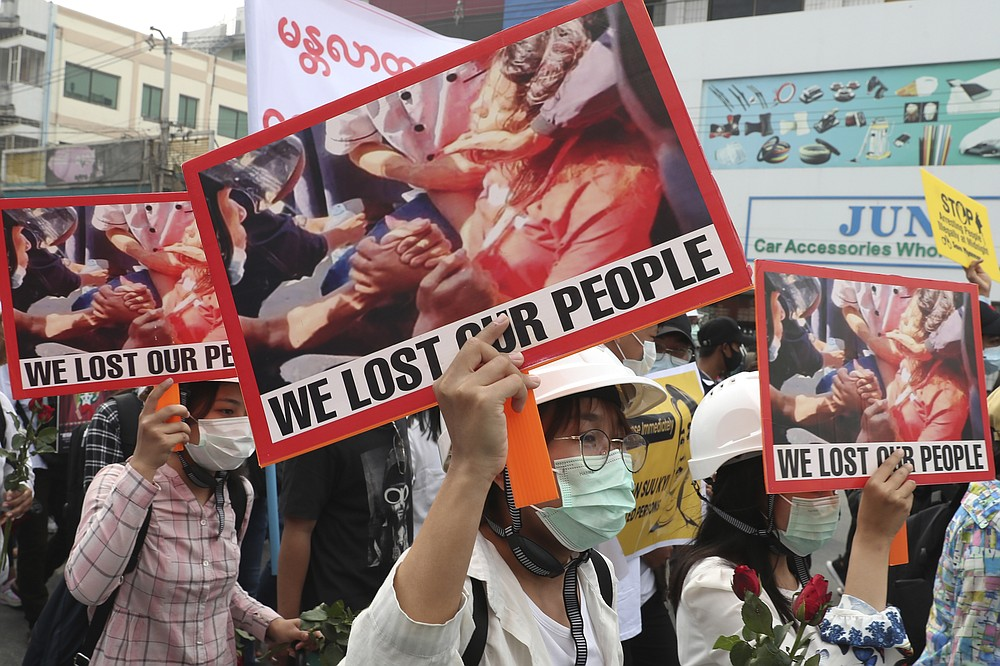 "Anti-coup protesters hold an image of Mya Thwet Thwet Khine with a sign that reads ""We Lost Our People"" during an anti-coup protest rally in Mandalay, Myanmar Saturday, Feb. 20, 2021. Anti-coup protesters in Myanmar's two largest cities on Saturday paid tribute to the young woman who died a day earlier after being shot by police during a rally against the military takeover. (AP Photo)"