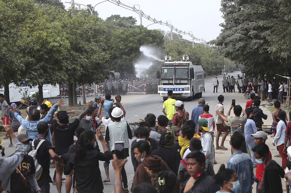 A police truck uses a water cannon to disperse protesters in Mandalay, Myanmar, on Saturday, Feb. 20, 2021. Security forces in Myanmar ratcheted up their pressure against anti-coup protesters Saturday, using water cannons, tear gas, slingshots and rubber bullets against demonstrators and striking dock workers in Mandalay, the nation's second-largest city. (AP Photos)