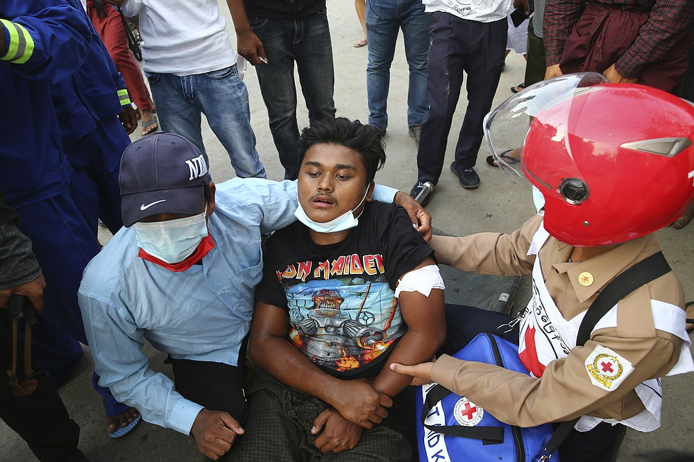 A man is provided with first aid during a protest in Mandalay, Myanmar on Saturday, Feb. 20, 2021. Security forces in Myanmar ratcheted up their pressure against anti-coup protesters Saturday, using water cannons, tear gas, slingshots and rubber bullets against demonstrators and striking dock workers in Mandalay, the nation's second-largest city. (AP Photos)