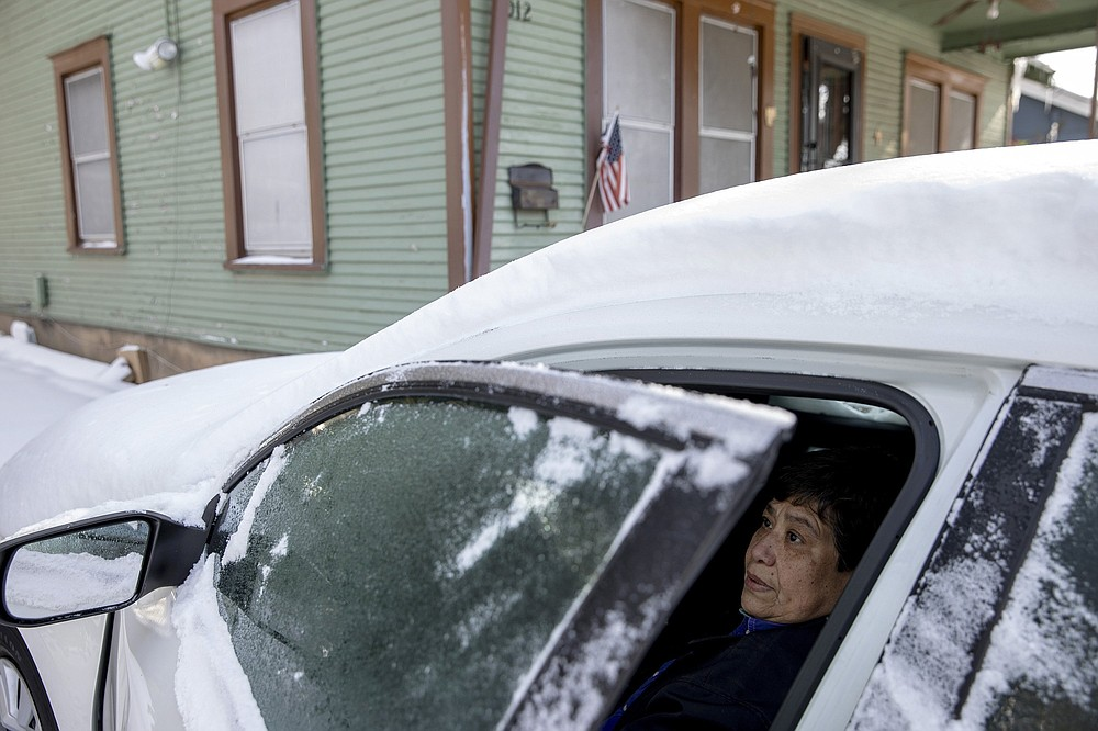 FILE - In this Tuesday, Feb. 16, 2021, file photo, Maria Pineda warms up in her car outside her home in East Austin, Texas, during a power outage caused by a winter storm. Pineda said her home has been without power since early Monday morning. (Jay Janner/Austin American-Statesman via AP, File)