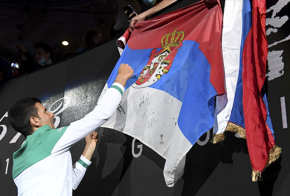 Serbia's Novak Djokovic signs autographs after defeating Russia's Daniil Medvedev during the men's singles final at the Australian Open tennis championship in Melbourne, Australia, Sunday, Feb. 21, 2021.(AP Photo/Andy Brownbill)