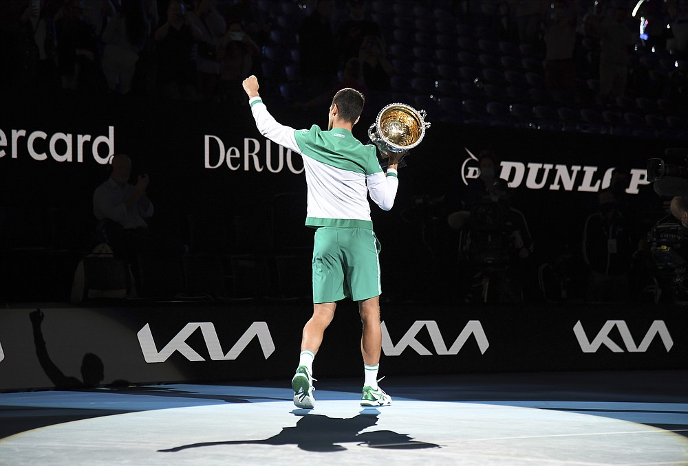Serbia's Novak Djokovic holds the Norman Brookes Challenge Cup aloft after defeating Russia's Daniil Medvedev in the men's singles final at the Australian Open tennis championship in Melbourne, Australia, Sunday, Feb. 21, 2021.(AP Photo/Andy Brownbill)