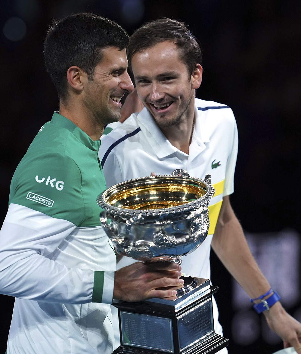 Serbia's Novak Djokovic, left, holds the Norman Brookes Challenge Cup as he talks with runner-up Russia's Daniil Medvedev after winning the men's singles final at the Australian Open tennis championship in Melbourne, Australia, Sunday, Feb. 21, 2021.(AP Photo/Mark Dadswell)