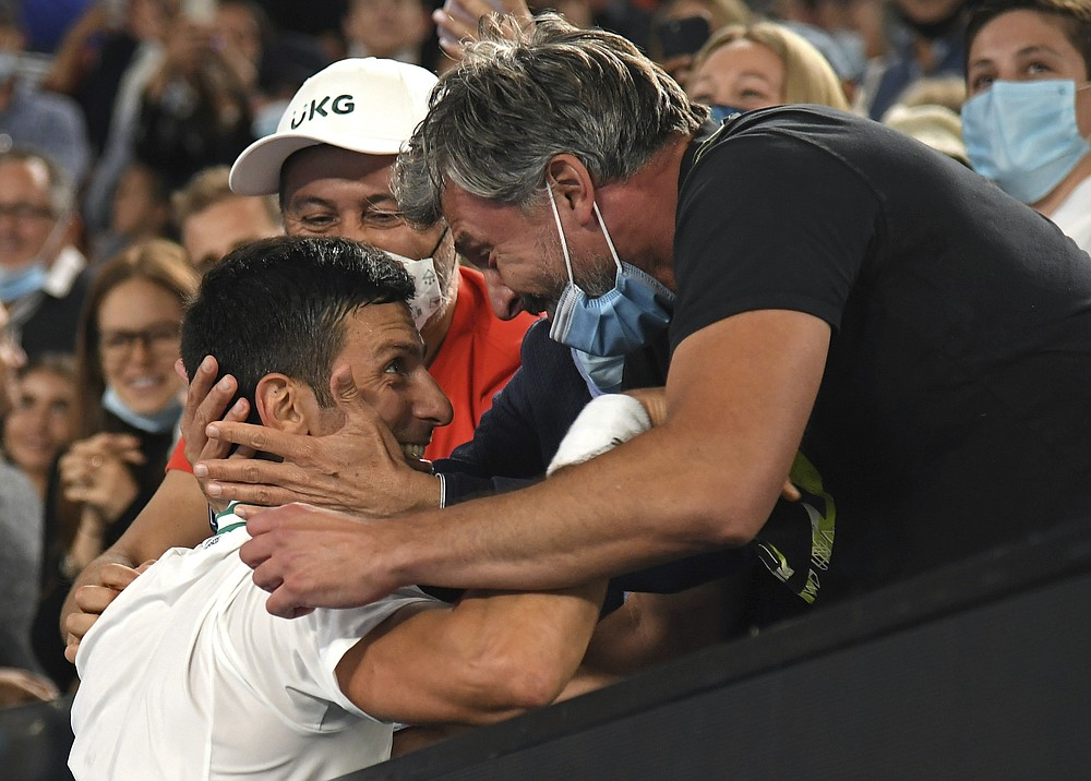 Serbia's Novak Djokovic celebrates with Goran Ivanisevic, right, and his support team after defeating Russia's Daniil Medvedev in the men's singles final at the Australian Open tennis championship in Melbourne, Australia, Sunday, Feb. 21, 2021.(AP Photo/Andy Brownbill)