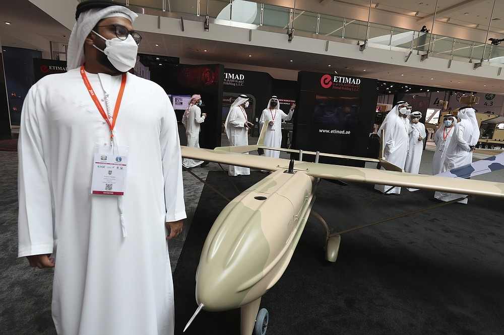 Visitors and officials pass by a combat drone from Etmad, an Emirati company, during the opening day of the International Defence Exhibition & Conference, IDEX, in Abu Dhabi, United Arab Emirates, Sunday, Feb. 21, 2021. (AP Photo/Kamran Jebreili)