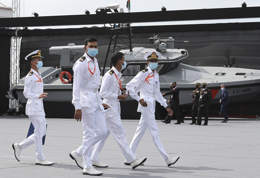 Navy officers walk past a combat boat built by Alfattan in the UAE, on the opening day of the regions leading naval defence and maritime security event, NAVDEX, in Abu Dhabi, United Arab Emirates, Sunday, Feb. 21, 2021. (AP Photo/Kamran Jebreili)