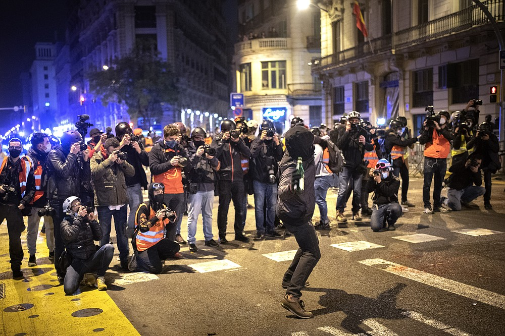 Media take images as a man throws a bottle agains a national police station during clashes following a protest condemning the arrest of rap singer Pablo Hasél in Barcelona, Spain, Sunday, Feb. 21, 2021. Protests in support of a jailed rapper turned violent for a sixth consecutive night in Barcelona on Sunday with clashes between police and groups of mostly angry youths in the center of the Spanish city. (AP Photo/Emilio Morenatti)