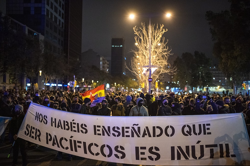 "Demonstrators march holding a banner reading ""you have taught us that being peaceful is useless"" during a protest condemning the arrest of rap singer Pablo Hasél in Barcelona, Spain, Sunday, Feb. 21, 2021. Protests in support of a jailed rapper turned violent for a sixth consecutive night in Barcelona on Sunday with clashes between police and groups of mostly angry youths in the center of the Spanish city. (AP Photo/Emilio Morenatti)"