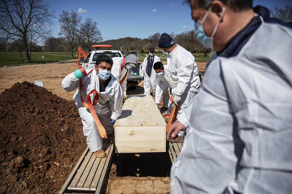 FILE - In this April 6, 2020, file photo, gravediggers lower the casket of someone who died of coronavirus at the Hebrew Free Burial Association's cemetery in the Staten Island borough of New York. The U.S. death toll from COVID-19 has topped 500,000 — a number so staggering that a top health researchers says it is hard to imagine an American who hasn't lost a relative or doesn't know someone who died. (AP Photo/David Goldman, File)