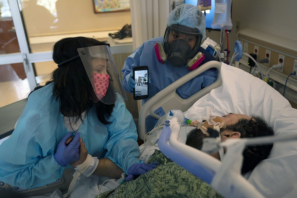 "FILE - In this Feb. 15, 2021, file photo, Patty Trejo, 54, left, looks at her intubated husband, Joseph, in a COVID-19 unit as registered nurse Celina Mande holds a smartphone showing a mariachi band performing for the patient at St. Jude Medical Center, in Fullerton, Calif. Trejo visited her husband for the first time since he was hospitalized more than a month ago. A survivor of COVID-19 herself, she invited a mariachi band to give him courage. Surrounded by hospital staff, family members and friends in the parking lot of the hospital, the band played her husband's favorite song, ""La mano de Dios,"" or ""The Hand of God."" ""He needs to know that I still love him, and he needs to know he's got to fight,"" said Trejo. (AP Photo/Jae C. Hong, File)"