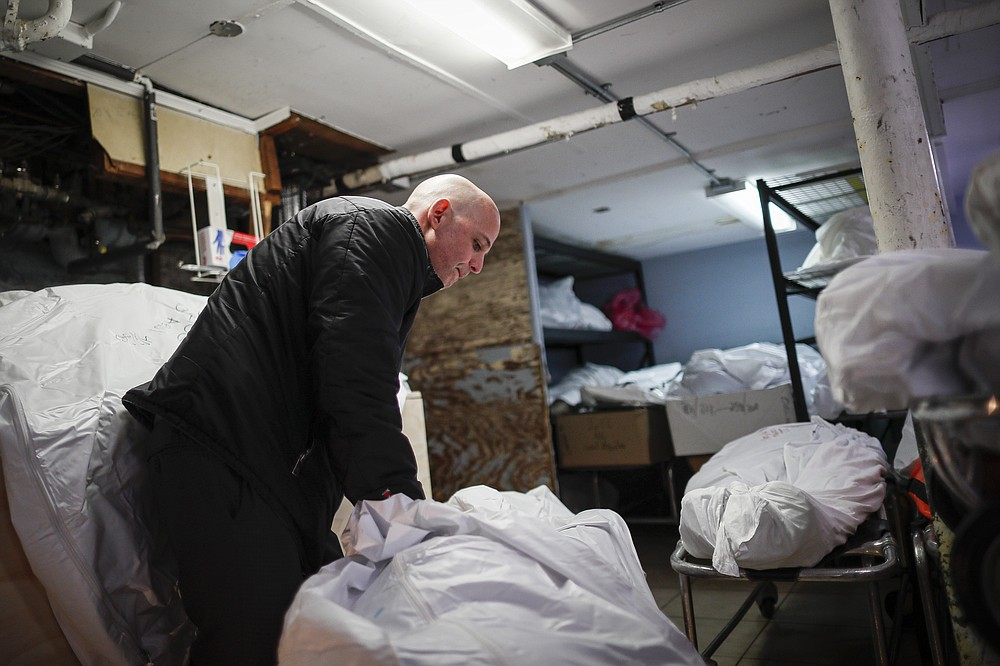 FILE - In this April 2, 2020, file photo, Pat Marmo, owner of Daniel J. Schaefer Funeral Home, walks through his body holding facility in the Brooklyn borough of New York. The U.S. death toll from COVID-19 has topped 500,000 — a number so staggering that a top health researchers says it is hard to imagine an American who hasn't lost a relative or doesn't know someone who died. (AP Photo/John Minchillo, File)