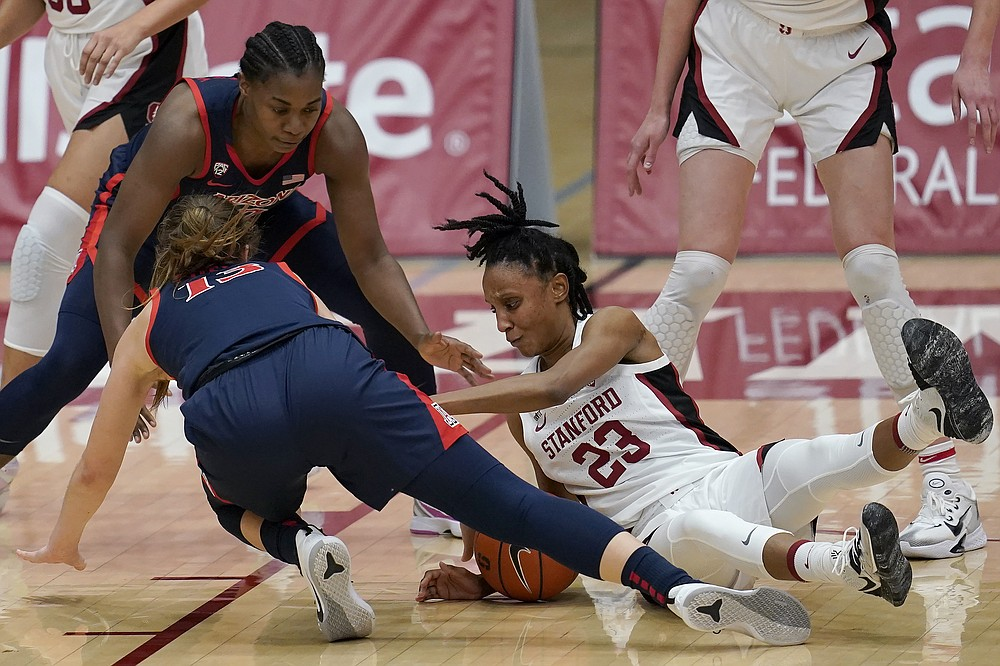 Stanford guard Kiana Williams, right, reaches for the ball under Arizona guard Helena Pueyo, bottom left, and forward Trinity Baptiste during the first half of an NCAA college basketball game in Stanford, Calif., Monday, Feb. 22, 2021. (AP Photo/Jeff Chiu)