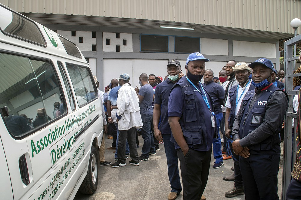 Colleagues of World Food Programme (WFP) driver Moustapha Milambo, who was killed in the attack on a U.N. convoy that also killed the Italian ambassador to Congo and an Italian Carabinieri police officer, wait to receive his body at the morgue in Goma, North Kivu province, Congo Tuesday, Feb. 23, 2021. An Italian Carabinieri unit is expected in Congo Tuesday to investigate the killings of the Italian ambassador to Congo, an Italian Carabinieri police officer and their driver in the country's east. (AP Photo/Justin Kabumba)