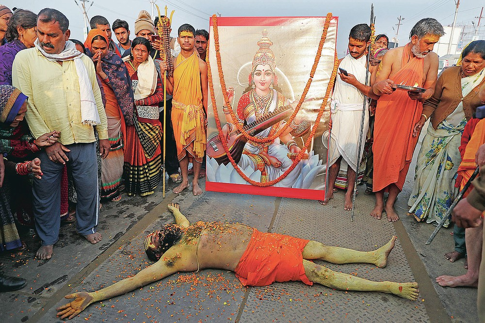 A Hindu Holy man lies in front of an image of Hindu Goddess of learning Saraswati, at Sangam, the sacred confluence of the rivers Ganga, Yamuna and the mythical Saraswati, during Magh Mela festival, in Prayagraj, India. Tuesday, Feb. 16, 2021. Hindus believe that ritual bathing on auspicious days can cleanse them of all sins. A tented city for the religious leaders and the believers has come up at the sprawling festival site with mounted police personnel keeping a close watch on the activities. The festival is being held amid rising COVID-19 cases in some parts of India after months of a steady nationwide decline. (AP Photo/Rajesh Kumar Singh)
