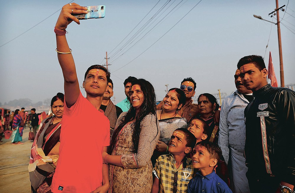A family takes a selfie after a holy dip at Sangam during Magh mela festival, in Prayagraj, India. Friday, Feb. 19, 2021.  Millions of people have joined a 45-day long Hindu bathing festival in this northern Indian city, where devotees take a holy dip at Sangam, the sacred confluence of the rivers Ganga, Yamuna and the mythical Saraswati. Here, they bathe on certain days considered to be auspicious in the belief that they be cleansed of all sins. (AP Photo/Rajesh Kumar Singh)