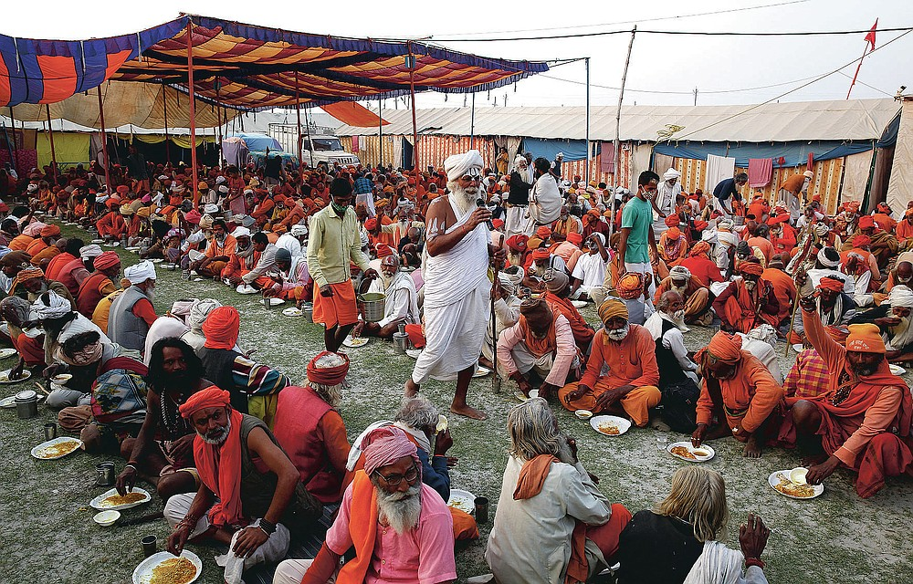 Devotees and pilgrims eat at a free food camp, at Sangam, during Magh Mela festival, in Prayagraj, India. Friday, Feb. 19, 2021.  Millions of people have joined a 45-day long Hindu bathing festival in this northern Indian city, where devotees take a holy dip at Sangam, the sacred confluence of the rivers Ganga, Yamuna and the mythical Saraswati. Here, they bathe on certain days considered to be auspicious in the belief that they be cleansed of all sins. (AP Photo/Rajesh Kumar Singh)