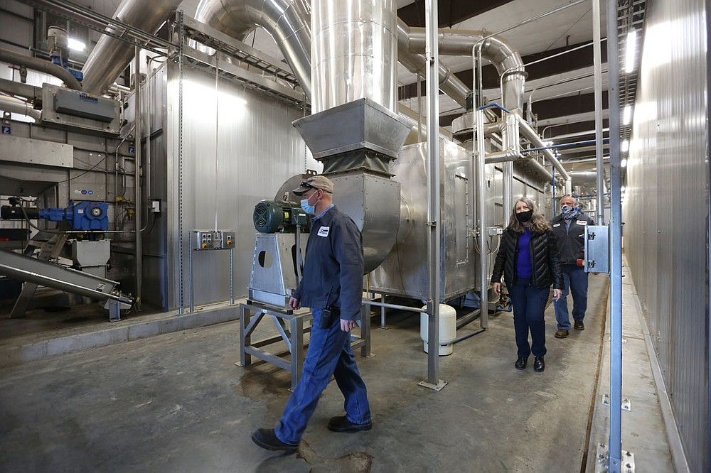 Jere Orvin (from left), operations supervisor at the Springdale Wastewater Treatment Facility, Jennifer Enos, facilities director, and Loren Sharp, operations manager, walk Thursday, February 25, 2021, through the biosolids huber dryer inside the Dryer Building at the facility on Silent Grove Road in Springdale. The biosolids huber dryer is the largest in North America. Check out nwadg.com/photos for a photo gallery. (NWA Democrat-Gazette/David Gottschalk)