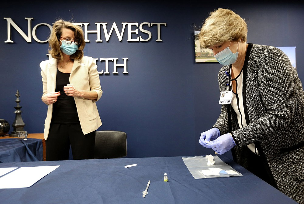 Susan Kristiniak (right), assistant chief nursing officer at Northwest Health in Springdale, prepares to administer a covid-19 vaccine Friday, Dec. 18, 2020, to Dr. Marti Sharkey, city of Fayetteville public health officer, at the medical center in Springdale. Check out nwaonline.com/201219Daily/ and nwadg.com/photos for a photo gallery. (NWA Democrat-Gazette/David Gottschalk)