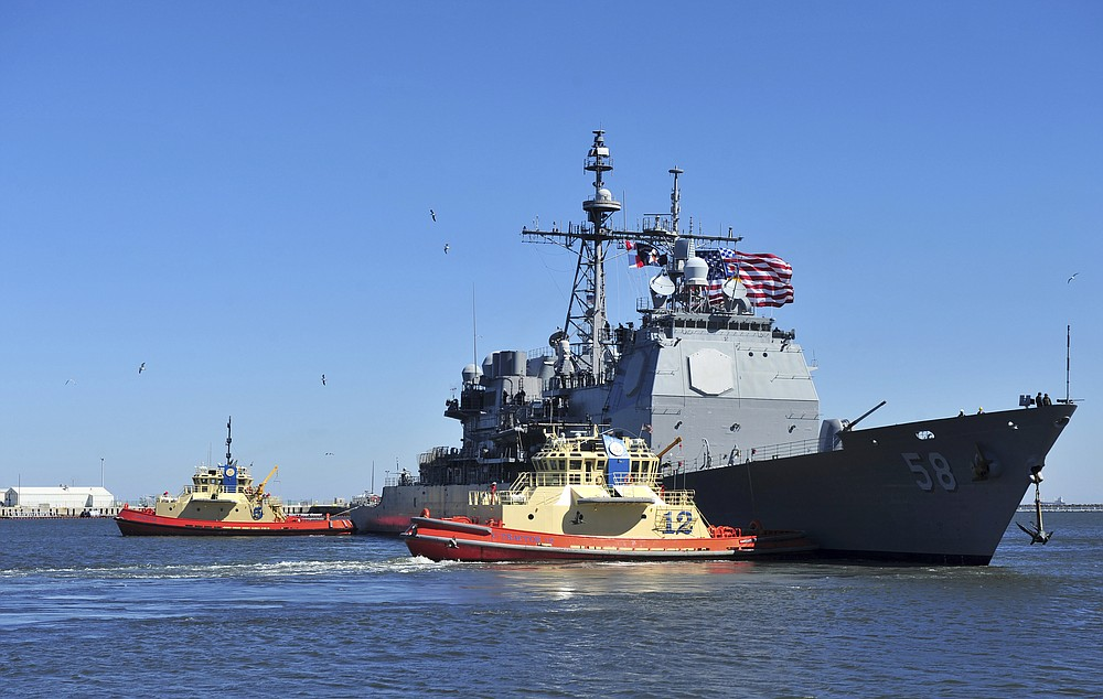 """In this Feb. 15, 2014, photo released by the U.S. Navy, the guided-missile cruiser USS Philippine Sea leaves Naval Station Mayport in Mayport, Florida. Two U.S. Navy warships operating in the Mideast have been affected by the coronavirus, authorities said Friday, Feb. 26, 2021, with one already at port in Bahrain and another heading to port. The Philippine Sea will head to a port that the Navy declined to name over """"operational security."""" (Mass Communication Specialist 2nd Class Marcus L. Stanley/U.S. Navy, via AP)"""