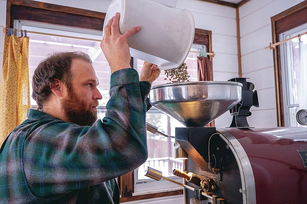 Erik Johnson loads his coffee bean roaster with a batch of raw Tanzania Peaberry beans in his roasting studio at his home, Wednesday, Feb. 10, 2021, in Waverly, Iowa. Along with his wife, Becky, the pair are sharing their creations with other coffee lovers at Thinkwell, an online ordering system where customers can purchase customized coffee beans.  (Chris Zoeller/Globe-Gazette via AP)