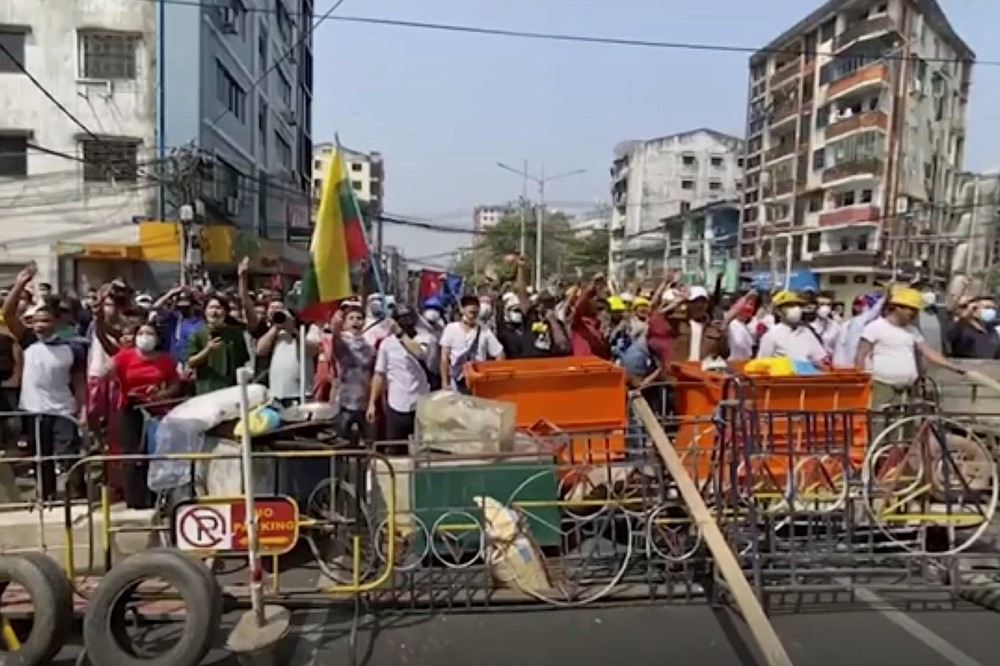 In this image made from video, anti-coup protesters shout at police in Yangon, Myanmar, Saturday, Feb. 27, 2021. Myanmar police on Saturday moved to clear anti-coup protesters from the streets of the country's biggest city Yangon. (AP Photo)