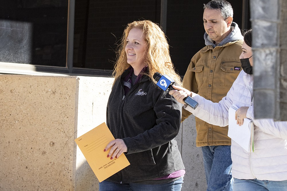 FILE - In this Jan. 13, 2021 file photo, Jenny Cudd, a flower shop owner and former Midland mayoral candidate, and Eliel Rosa leave the federal courthouse in Midland, Texas. A federal judge on Friday, Feb. 5, 2021 gave permission for Jenny Cudd, a West Texas flower shop owner charged in last month's riot at the U.S. Capitol to take a work-related four-day trip to Mexico. (Jacob Ford/Odessa American via AP, File)