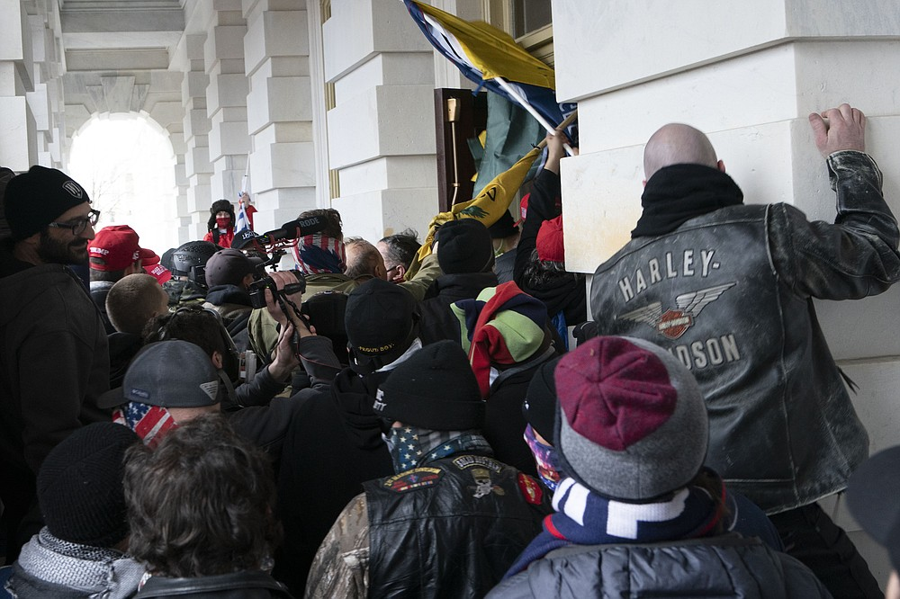 FILE - In this Jan. 6, 2021 file photo insurrectionists loyal to President Donald Trump try to open a door of the U.S. Capitol as they riot in Washington. (AP Photo/Jose Luis Magana, File)