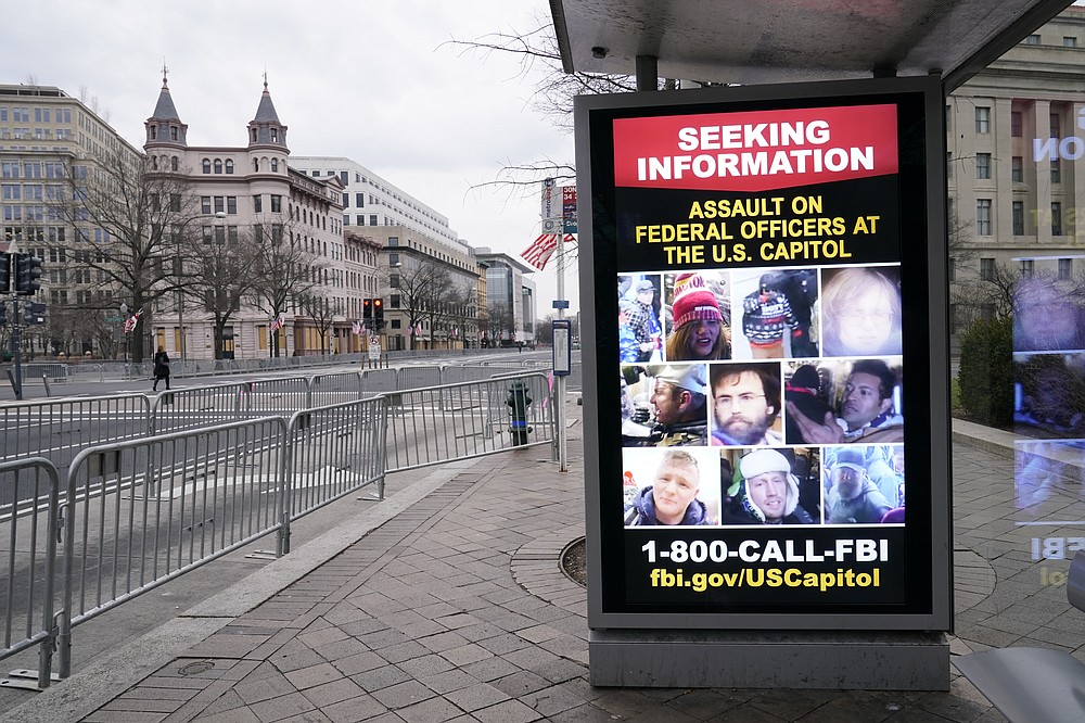 FILE- In this Jan. 15, 2021, file photo a bus stop along Pennsylvania Avenue shows a poster from the FBI in Washington. (AP Photo/Susan Walsh, File)