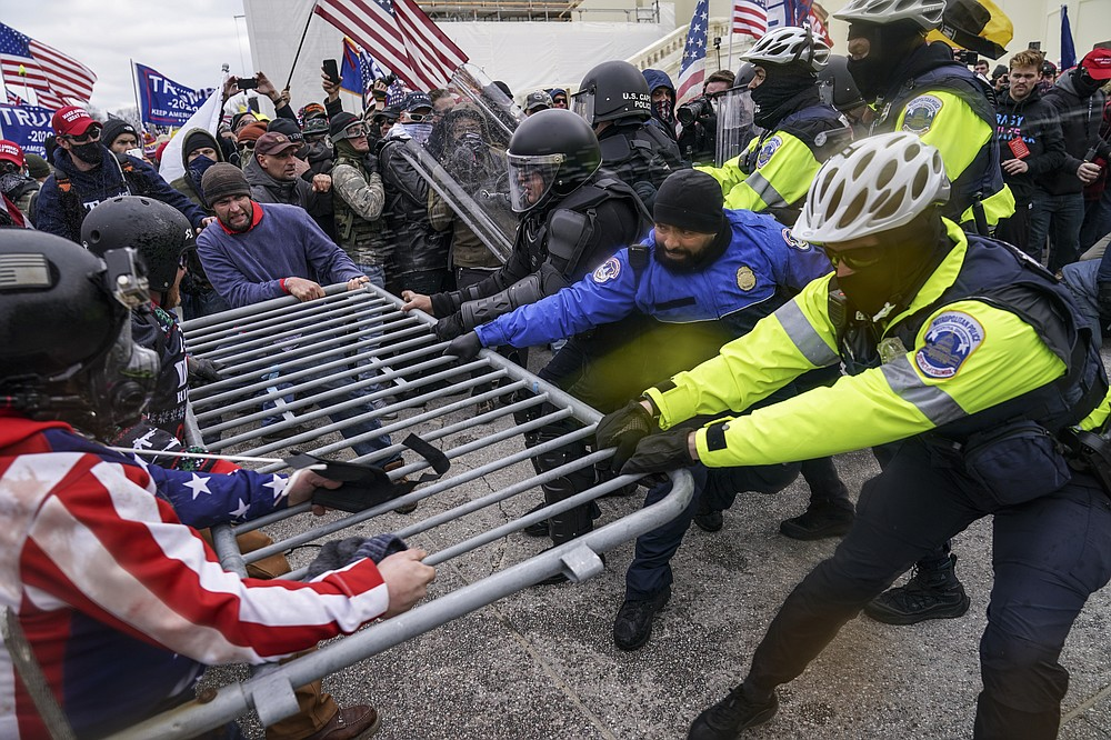 FILE - In this Jan. 6, 2021, file photo rioters try to break through a police barrier at the Capitol in Washington. Congress is set to hear from former security officials about what went wrong at the U.S. Capitol on Jan. 6. (AP Photo/John Minchillo, File)