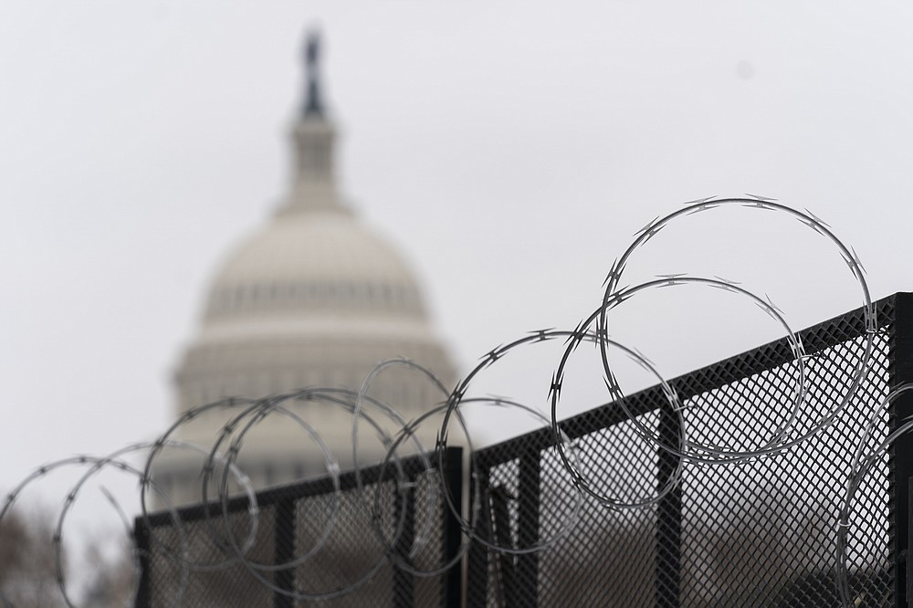 FILE - In this Feb. 18, 2021, file photo the U.S. Capitol is seen behind the razor fence around the U.S. Capitol. (AP Photo/Manuel Balce Ceneta, File)