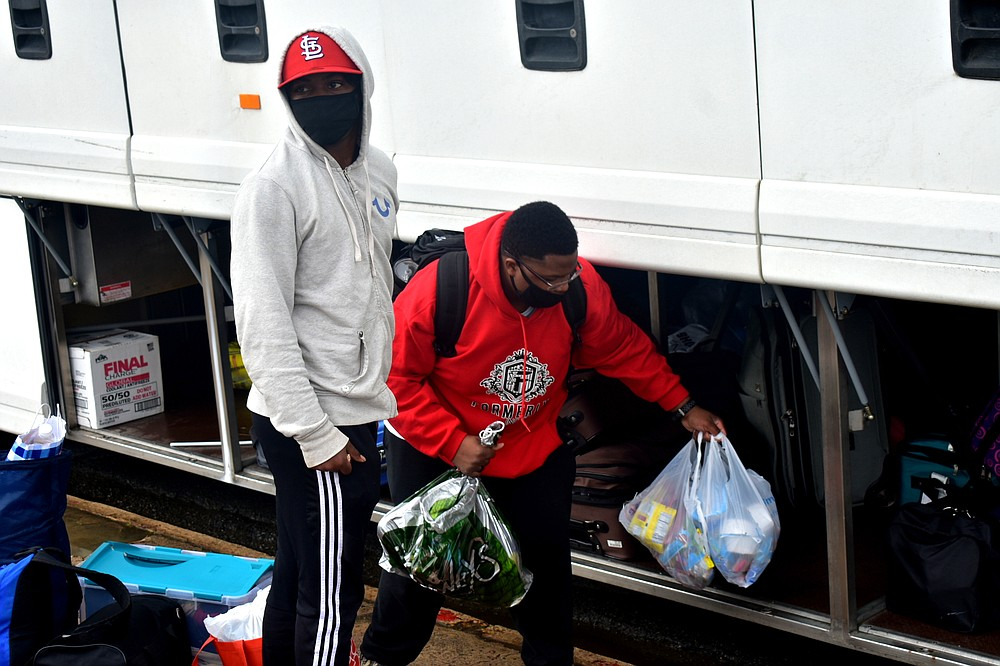 From left, freshmen Terry Norwood, 19, of Memphis, and Jonathan Whitney, 18, of Camden unload the bus after returning from a Little Rock hotel to Harrold Complex at the University of Arkansas at Pine Bluff on Sunday, Feb. 28, 2021. (Pine Bluff Commercial/I.C. Murrell)