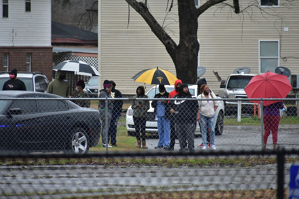 Bystanders look on from Sulphur Springs Road after a report of a shooting at Watson Chapel Junior High School on Monday. (Pine Bluff Commercial/I.C. Murrell)